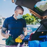 Un homme portant un masque en sortant de l'épicerie place ses achats dans le coffre ouvert de sa voiture.