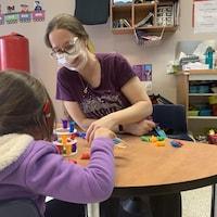 Une femme porte un masque à fenêtre et sourit. Elle est assise à une table avec une enfant et elles manipulent de petites figurines.