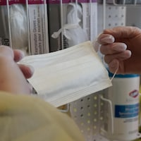 Un préposé aux bénéficiaires s'apprête à mettre un masque de protection.