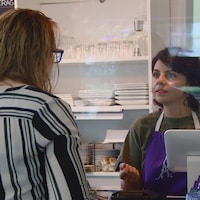 Une caissière parle à un client, ils sont séparés par un plexiglas.
