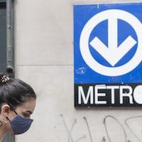 Une femmes portent un masque devant une affiche du métro.