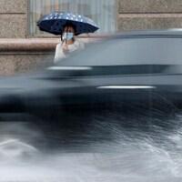 Une passante portant un masque sous la pluie.