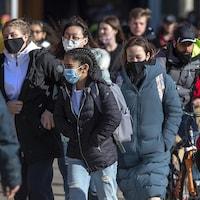 Un groupe de gens marchent sur un trottoir. Une personne est à vélo.