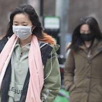 Deux femmes portent un masque chirurgical en marchant dans la rue à Toronto.