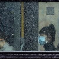 Des gens,que l'on aperçoit à travers une fenêtre embuée par la pluie, portent un masque dans un autobus de Vancouver.