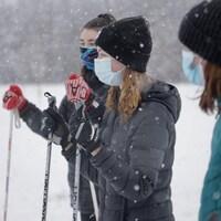 Trois amies font du ski de fond sous la neige.