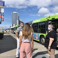 Un homme masqué parle avec deux femmes aussi masquées sur un trottoir à un arrêt d'autobus. Un bus passe derrière eux.