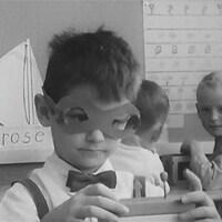 Un garçon, masque de papier sur les yeux, s'amuse avec des blocs dans une classe de maternelle.