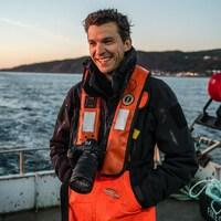Le photographe Mathieu Dupuis sur un bateau de pêche, caméra autour du cou.