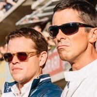 Deux hommes se tiennent debout devant une foule dans des gradins et fixent l'horizon du regard.
