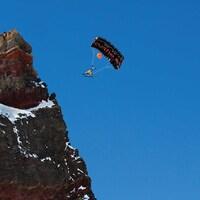 un homme faisant du ski-BASE jump, en parachute.