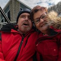 On voit le couple assis dans une balançoire derrière la maison. Ils sourient à la caméra.