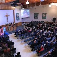 Vue élevée sur les sièges et l'autel d'une église de Saskatoon avec des gens qui sont assis et écoutent un pianiste et un chanteur.