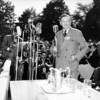 Maurice Duplessis prononce un discours debout derrière une série de micros sur pied lors de l'inauguration du pont Duplessis le 6 juin 1948. Derrière lui, on voit des photographes et le public, assis, venu assister à l'événement.