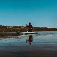 Une femme est assise sur une planche à Pagaie dans le milieu d'un lac.
