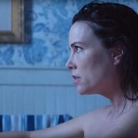 Une femme assise dans un bain affiche un air troublé.