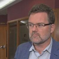 Un homme dans l'hôtel de ville de Gatineau en entrevue avec un média.