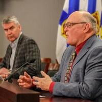 Les deux hommes donnent une conférence de presse. M. McNeil écoute le Dr Strang qui s'adresse aux journalistes.