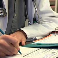 Un médecin remplissant un rapport à son bureau.