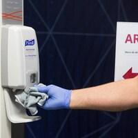 Une main gantée nettoie la base d'un distributeur de désinfectant.