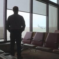 Le responsable de l'aéroport de Medicine Hat, Jeff Huntus, regarde un jet privé sur la piste depuis la salle d'attente vide.