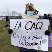 """Mélissa Bernier porte une affiche où on peut lire """"La CAQ on en a plein la couche"""""""