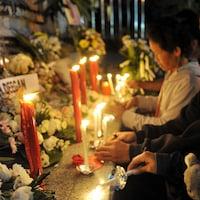 Des personnes se recueillent devant un mémorial avec des fleurs et des chandelles.