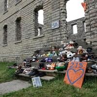 Des souliers et des jouets sont disposés sur les marches d'un bâtiment en ruines.