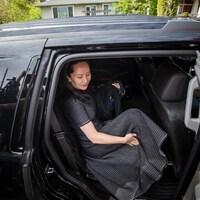 Une femme en robe entre dans une voiture noire.