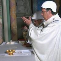 Portant un casque de protection, Mgr Michel Aupetit, archevêque de Paris, célèbre la première messe, deux mois après l'incendie dévastateur de la cathédrale Notre-Dame de Paris, samedi 15 juin 2019, à Paris.