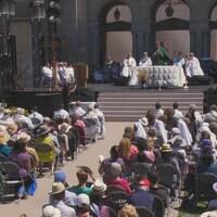 Un homme d'église célèbre la messe devant un parterre de fidèles.