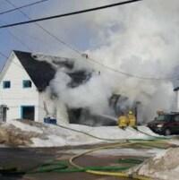Deux pompiers éteignent le feu dans une maison de Messines.