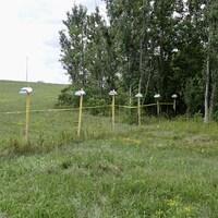 Des poteaux sur lesquels repose une petite boîte blanche et reliés entre eux par une corde.