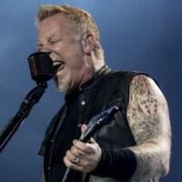 Une homme vêtu d'une veste noire sans manches tient une guitare et chante dans un microphone sur une scène de festival.