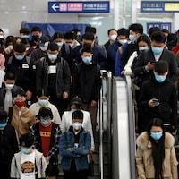 Une cinquantaine de personnes portant des masques descendent les escaliers.