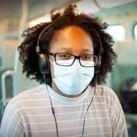 Une jeune femme portant un masque dans un train GO.