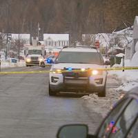 Scène de crime dans un quartier résidentiel de Québec. On aperçoit plusieurs véhicules de police stationnés dans la rue Sénégal. Un ruban jaune délimite le périmètre de sécurité.