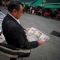 Un mariachi lit un journal dans une rue.