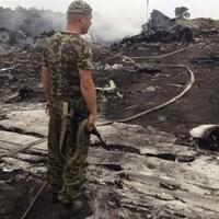 Un homme en treillis militaire et tenant une arme est debout au milieu de débris encore fumants.
