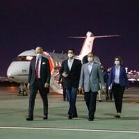 Dominic Barton, Michael Kovrig et Michael Spavor marchent sur le tarmac de l'aéoport en compagnie d'une femme.
