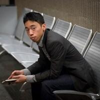 Michaël Nguyen est assis seul sur un banc.