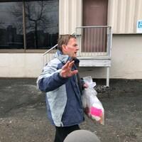 L'accusé, Michael Patrick McNutt, marche devant le palais de justice de Dartmouth en faisant un geste de la main pour éloigner les micros et caméras.