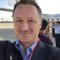 Michael Spavor se prend en photo devant un avion d'Air Koryo.