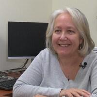 Madame Dubois est assise à son bureau, devant un ordinateur.