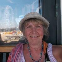 Une femme avec un chapeau sourit à la caméra.