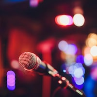Un micro sur une scène illuminée et festive.