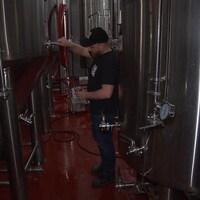 Un homme verse un verre de bière à partir d'une grande cuve dans une microbrasserie.