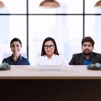 Cinq personnes, trois femmes et deux hommes, assises derrière une table de réunion.