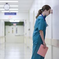 Une professionnelle de la santé est appuyée contre un mur dans un couloir d'hôpital.
