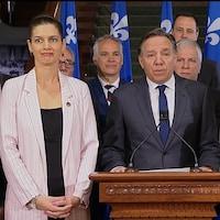 François Legault derrière un podium, entouré de son équipe de députés, lors d'une conférence de presse.